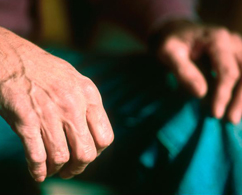 Photograph of old hands holding a teal napkin